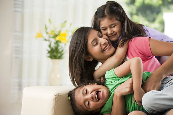 Mother With Daughters (6-7) Sitting On Sofa Art Print by ImagesBazaar