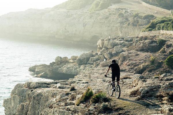 Wall Art - Photograph - Mountain Biker Riding On Coastal Cliffs by Daniel Santacatalina
