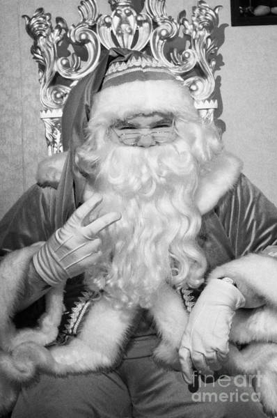Wall Art - Photograph - nasty Santa sitting on his throne holding two fingers up in grotto set up by Joe Fox