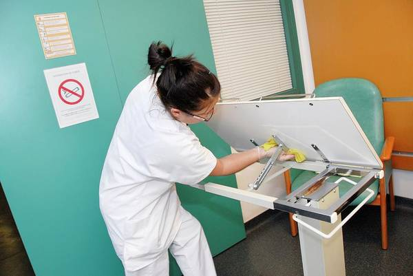 Wall Art - Photograph - Nurse Cleaning Hospital Table by Aj Photo/science Photo Library