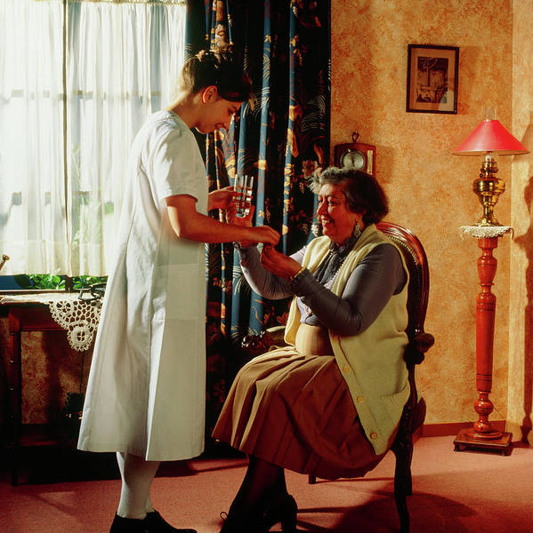 Senior Photograph - Nurse Gives Elderly Woman Her Medication At Home by Cc Studio/science Photo Library