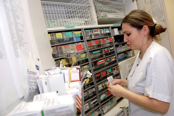 Wall Art - Photograph - Nurse Using A Drugs Cabinet by Aj Photo/science Photo Library