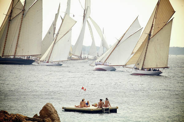 Sailing Photograph - People Sit On A Floating Dock And Watch by Patrick Swan / Design Pics