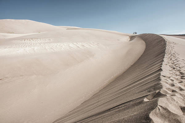 People Walking Photograph - People Walking On A Large Sand Dune by Tom Olson