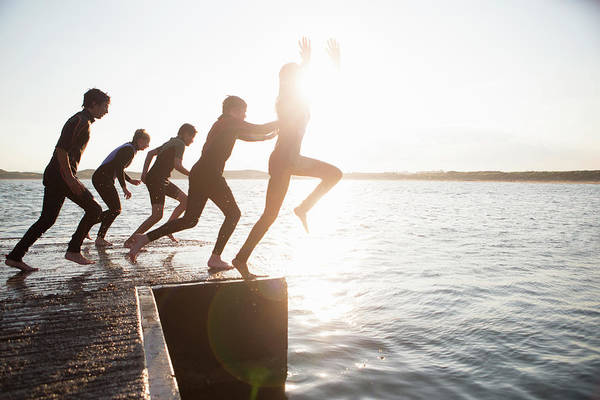 Adolescence Photograph - Pier Jumping by Solstock