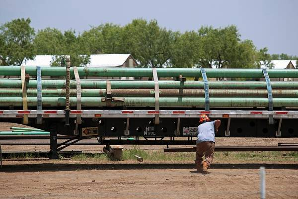 Trailer Photograph - Pipes Being Loaded On To A Truck by Jim West
