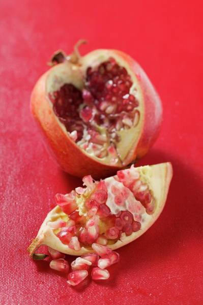 Wall Art - Photograph - Pomegranate, Cut Open, On Red Background by Foodcollection