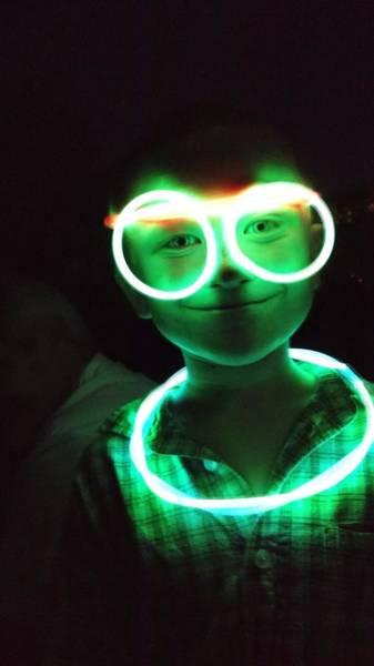 Portrait Of Boy With Illuminated Neon Ring And Eyeglasses In Darkroom Art Print by Sharon Kozik / EyeEm