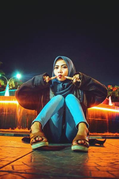 Portrait Of Young Woman Wearing Hijab While Sitting On Footpath At Night Art Print by Ilham Adhi Kusuma / EyeEm