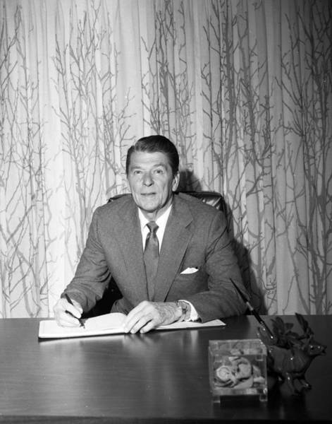 Republican Photograph - President Ronald Reagan Behind Desk by Retro Images Archive