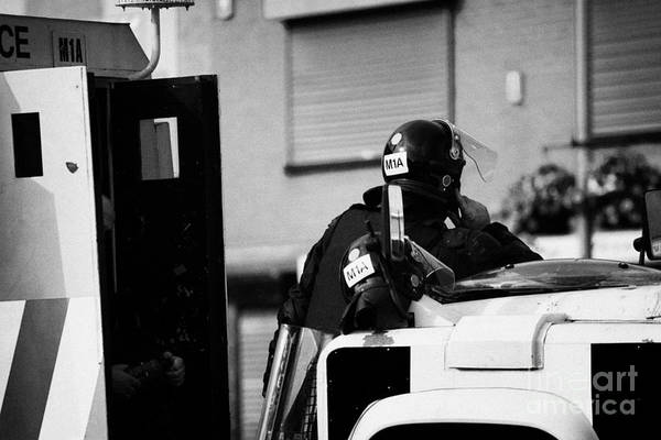 Turmoil Photograph - Psni Officer In Protective Riot Gear At Landrovers On Crumlin Road At Ardoyne Shops Belfast 12th Jul by Joe Fox