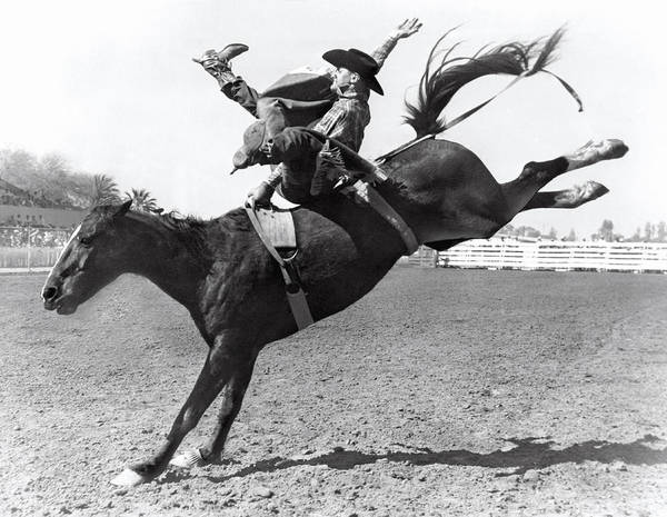 Jumping Photograph - Riding A Bucking Bronco by Underwood Archives