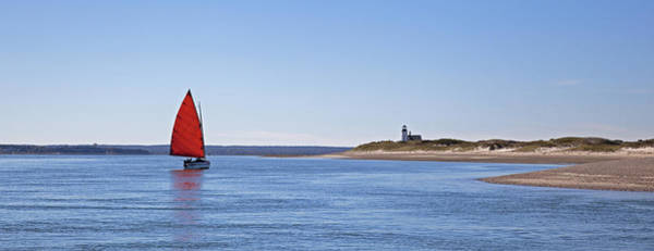 Photograph - Ripple Catboat With Red Sail And Lighthouse by Charles Harden