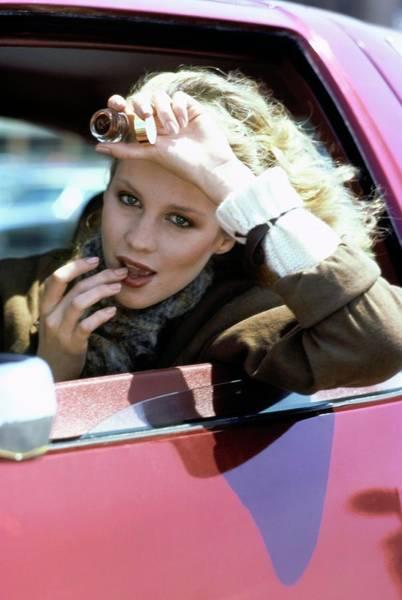 Apply Photograph - Rosie Vela Applying Lip Gloss by Arthur Elgort