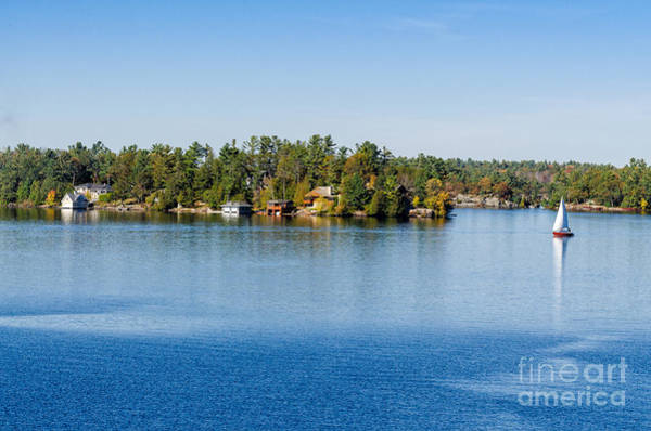 Photograph - Sailboat And A Row Of Boathouses Cottages by Les Palenik