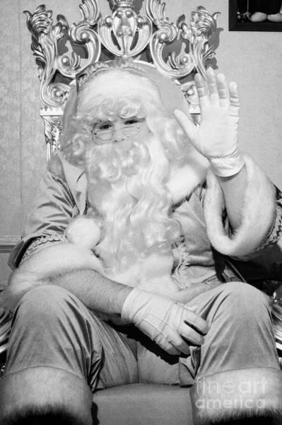 Wall Art - Photograph - Santa Sitting On His Throne Waving To Camera In Grotto Set Up by Joe Fox