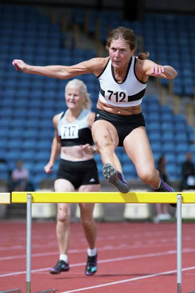 Determination Photograph - Senior Female Athlete Clears Hurdle by Alex Rotas