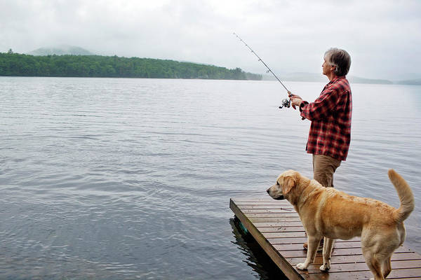 Wall Art - Photograph - Senior Man Fishing Off Dock With Dog by Monica Donovan