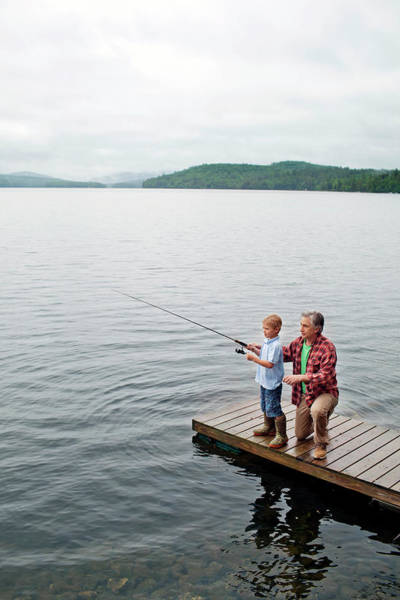 65 Photograph - Senior Man Showing Grandson How To Fish by Monica Donovan