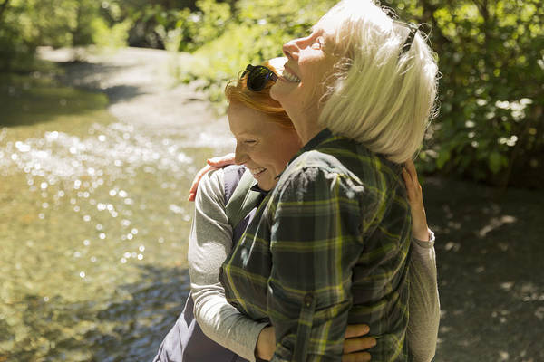 Senior Woman And Daughter Hiking Hugging By River Art Print by Compassionate Eye Foundation/Steven Errico