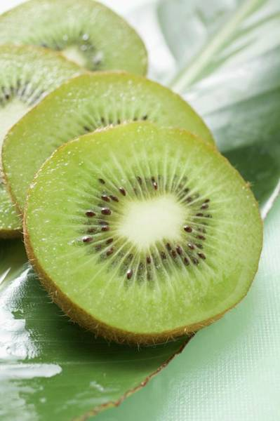 Kiwifruit Photograph - Several Slices Of Kiwi Fruit On Leaf by Foodcollection