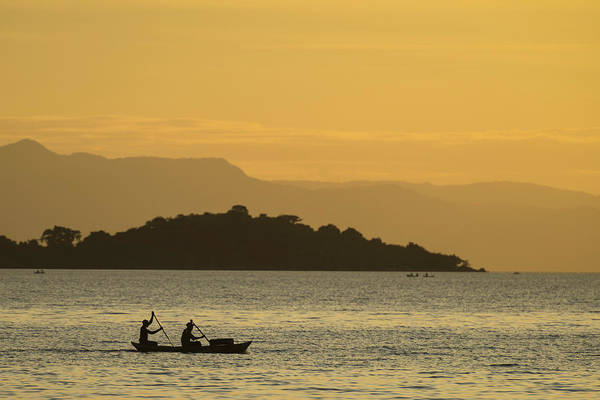 Wall Art - Photograph - Silhouette Of Fishermen In Dugout Canoe by Ian Cumming