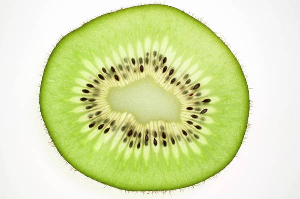 Kiwifruit Photograph - Slice Of Kiwi Fruit, Backlit by Foodcollection