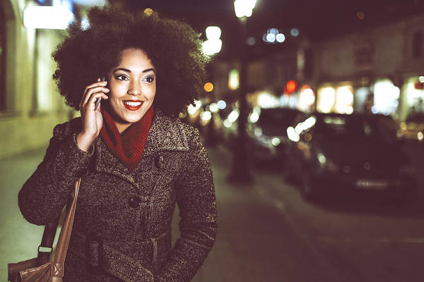 Smiling Young Woman Using Phone On Street By Night Art Print by Portishead1