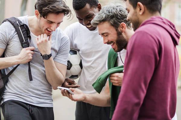 Sports Guys With Smart Phone Having Fun Art Print by Hinterhaus Productions