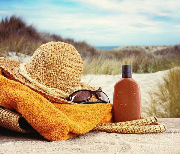 Photograph - Straw Hat With Towel And Lotion At The Beach  by Sandra Cunningham