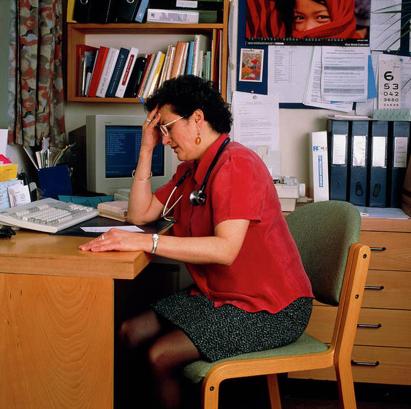 Wall Art - Photograph - Stressed Female Gp Doctor Working At Her Desk by Claire Paxton & Jacqui Farrow/science Photo Library