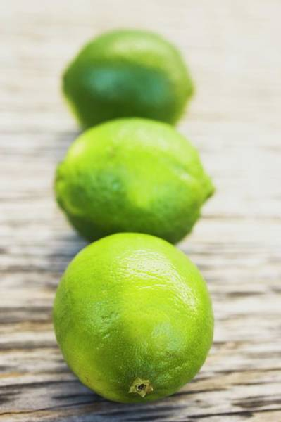 Wall Art - Photograph - Three Limes On Wooden Background by Foodcollection