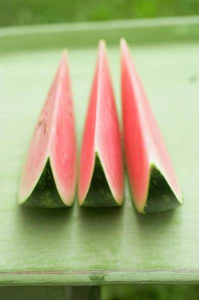 Watermellon Wall Art - Photograph - Three Wedges Of Watermelon On Green Table by Foodcollection