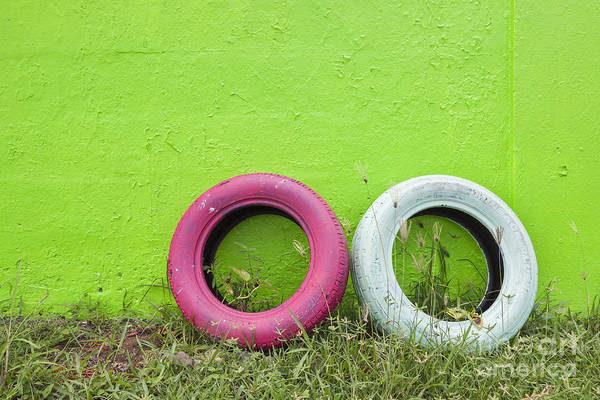Photograph - Tires Painted In Bright Color Leaning Against Wall In San Juan Pu by Bryan Mullennix