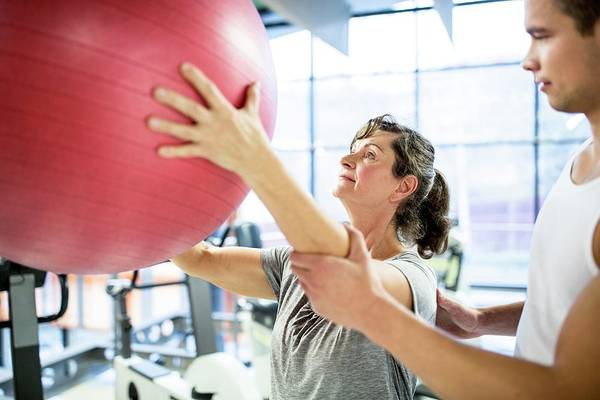 Improvement Photograph - Trainer Training Woman With Fitness Ball by Science Photo Library