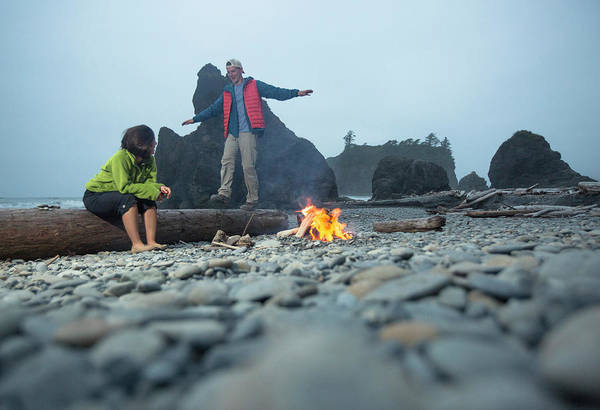 Wall Art - Photograph - Two Hikers Enjoy A Campfire On A Beach by Matt Andrew
