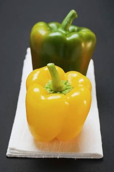 Wall Art - Photograph - Two Peppers (yellow, Green) On White Linen Cloth by Foodcollection
