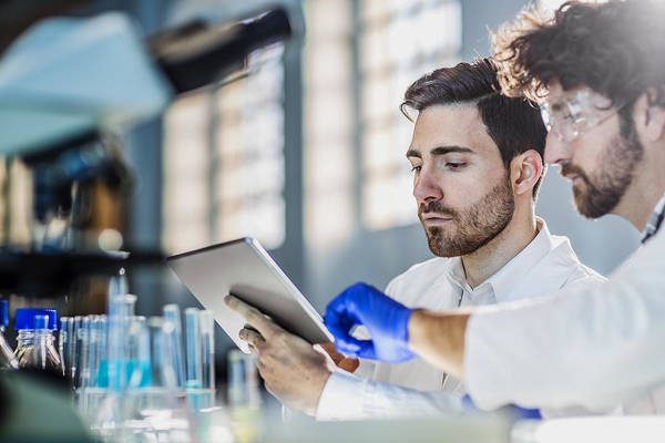 Two Scientist Using Digital Tablet In Laboratory Art Print by Poba