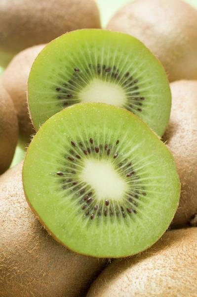 Kiwifruit Photograph - Two Slices Of Kiwi Fruit On Whole Kiwi Fruits by Foodcollection