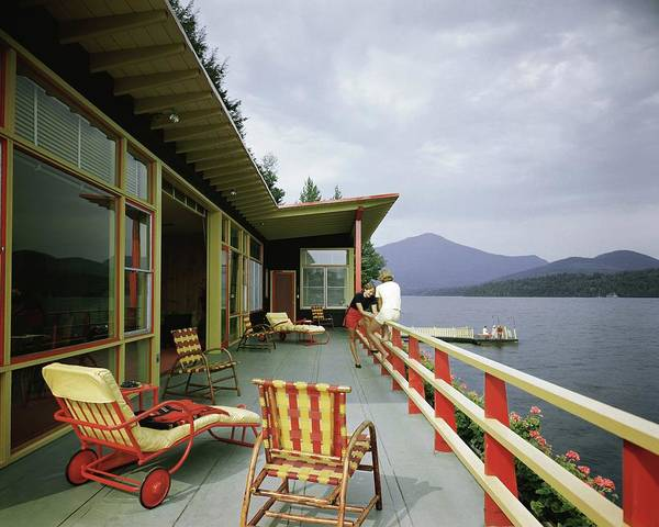 Furniture Photograph - Two Women On The Deck Of A House On A Lake by Robert M. Damora