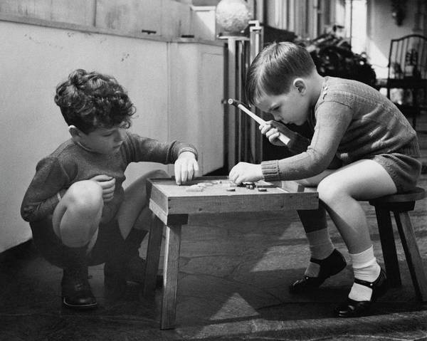 Old People Photograph - Two Young Boys Sitting By A Wooden Table by Remie Lohse
