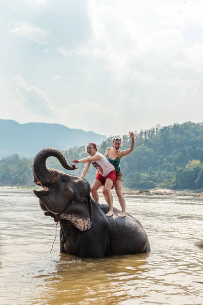 Two Young Women Riding An Elephant In The Mekong Art Print by Matteo Colombo