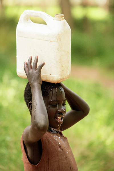 Wall Art - Photograph - Ugandan Child Carrying Water by Mauro Fermariello/science Photo Library