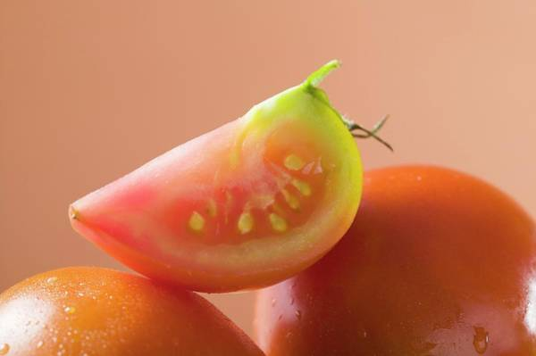 Vegies Photograph - Wedge Of Tomato On Whole Tomatoes by Foodcollection