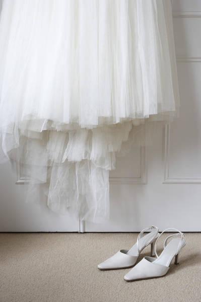 White Shoes On Floor Beneath Wedding Dress Hanging Outside Wardrobe Art Print by Michael Blann