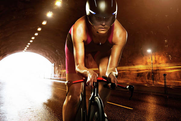 Helmet Photograph - Woman Cycling Through Tunnel by Johner Images