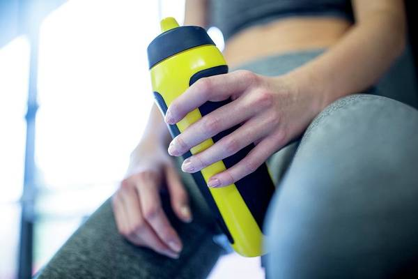 Concern Photograph - Woman Holding Water Bottle In Gym by Science Photo Library