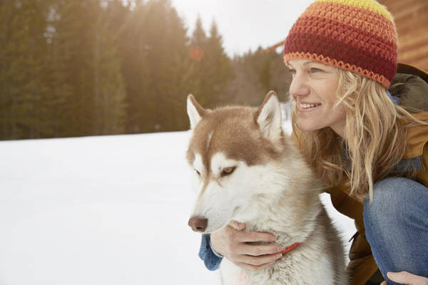 Woman Kneeling With Husky In Snow Covered Landscape, Elmau, Bavaria, Germany Art Print by Stephen Lux