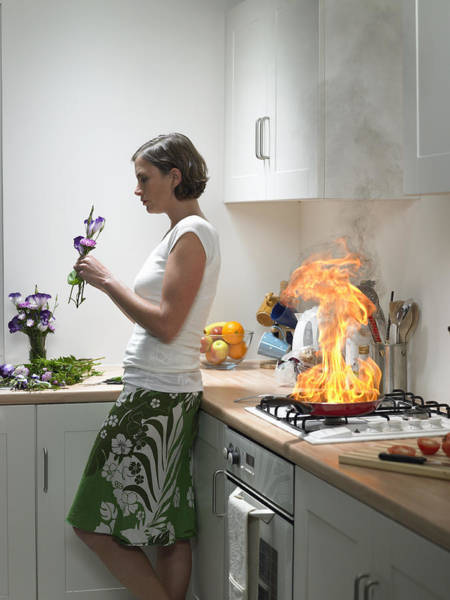 woman Leaning Against Kitchen Worktop Holding Flower, Frying Pan On Fire Behind Art Print by Michael Blann