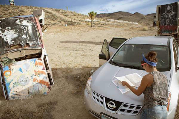 Buried Wall Art - Photograph - Woman Looking At Map At Nevada by Michael Okimoto
